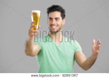 Intensional blured image of  young man tasting a draft beer