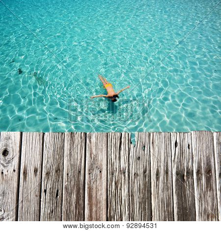 Woman snorkeling in crystal clear turquoise water at tropical beach