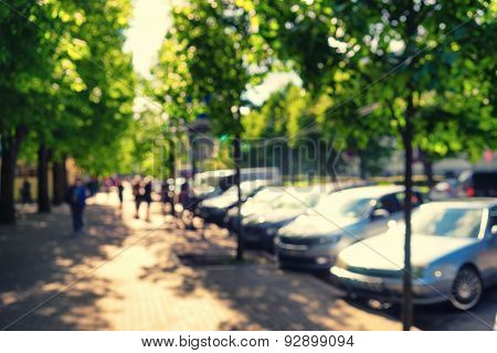 Cars Parked On The Street Near The Alley In The Park. Blurry