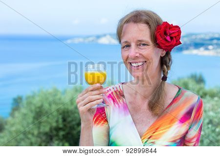 Woman with drink and red rose near sea