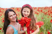 image of 7-year-old  - Mother and her 7 years old preteen child playing in spring flower field - JPG