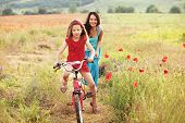 pic of preteens  - Preteen girl on bicycle with mother in spring field - JPG