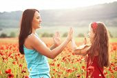 stock photo of preteen  - Mother and her 7 years old preteen child playing in spring poppy field in soft sunlight - JPG
