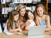 image of mums  - Little girls and their mum with a laptop in library - JPG