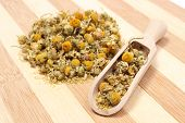 image of chamomile  - Dried chamomile heap of dried chamomile on wooden spoon - JPG
