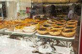 foto of custard  - Custard tarts in a shop window in Lisbon - JPG