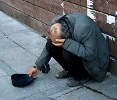 stock photo of beggars  - A Poor man begging on the street - JPG
