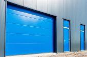 stock photo of roller shutter door  - blue shutter door in a modern commercial business unit - JPG