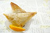 image of baklava  - Triangle shaped Turkish Baklava on a plate with decoupage background - JPG