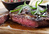 picture of rib eye steak  - medium roast rib-eye steak on wooden plate with pepper and salt