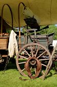 stock photo of wagon wheel  - The top has been removed from a covered wagon will of artifacts of the post Civil War era - JPG