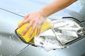 pic of soapy  - a man wash headlight of the car in car wash shop - JPG