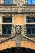 stock photo of building relief  - Famous reliefs on the facade with a reflection in the windows of the old town of Riga - JPG