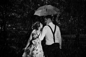 stock photo of flirt  - Young romantic couple in love flirting in rain - JPG