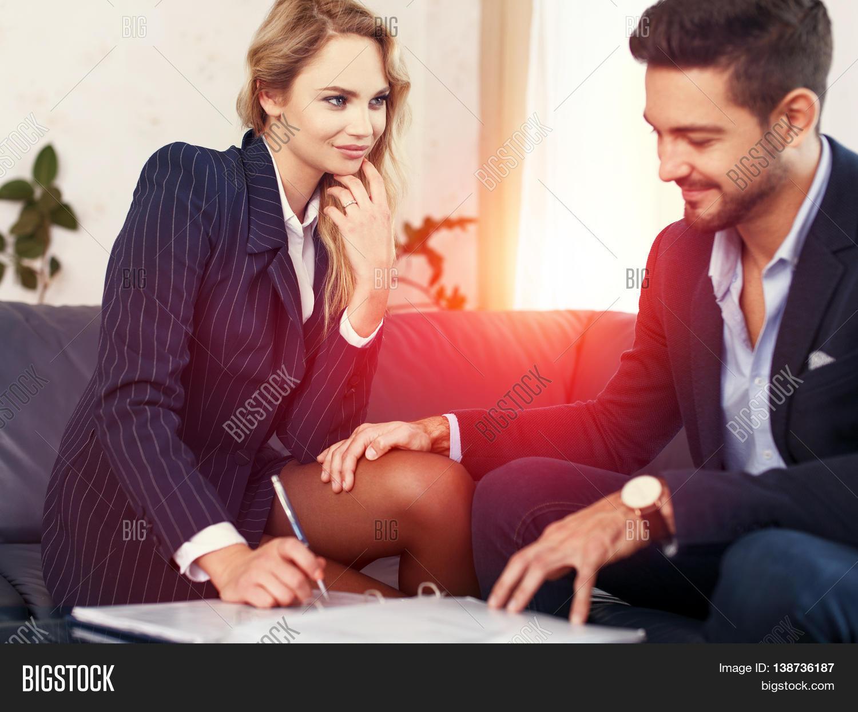 Businessman Seduce Businesswoman On Sofa Put Hand On Leg