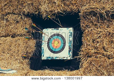 Archery target with arrows on rural shooting range outdoors on haystack background