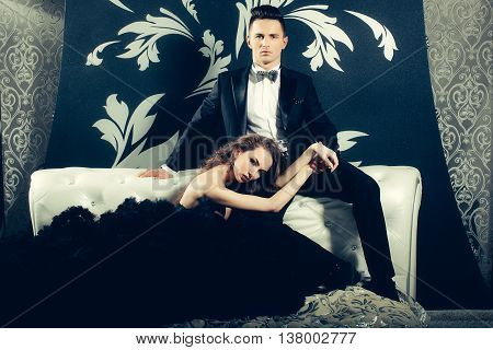 young handsome man in black suit and bow with pretty sexy woman in elegant evening dress with skirt and long curly hair on bed in bedroom