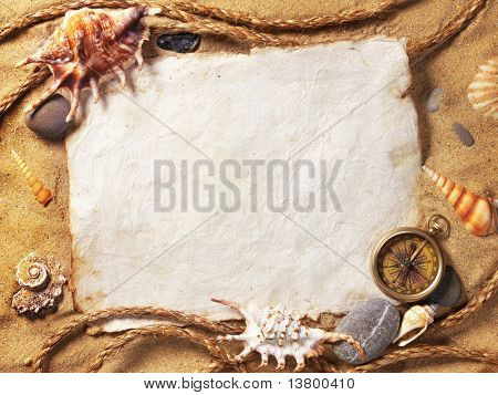 old paper, compass, shell and rope on sand background