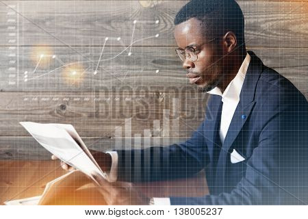 Visual Effects. Confident Dark-skinned Businessman Wearing Spectacles And Formal Wear, Reading Artic