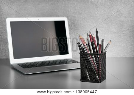 Pencils and pens in metal holder with laptop  on grey wall background