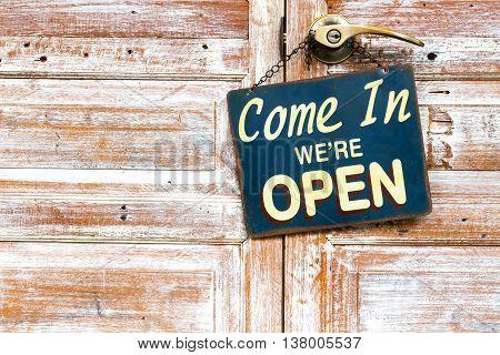 Come In We're Open on the wooden door copyspace on the left.