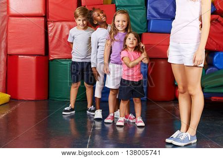 Children standing in a row in gym of preschool with PE teacher