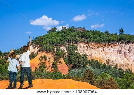 Brothers of seven and four years admire the magnificent nature. Orange and red picturesque hills. Languedoc - Roussillon, Provence, France