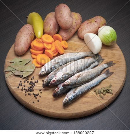 The classic ingredients for fishing soup. Fishes mullet, set of vegetables, black pepper and cardamom on a wooden round cutting board on dark brown wooden background.