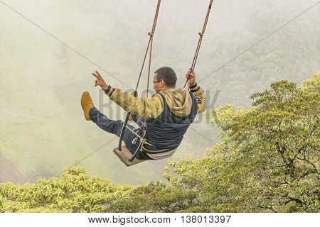 Young Man Swinging At Casa Del Arbol, Banos Ecuador