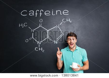 Smiling young man drinking coffee and pointing on drawn caffeine molecule chemical structure on chalkboard background