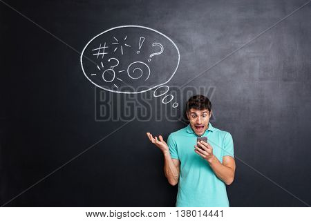 Crazy hysterical young man using smartphone and screaming over chalkboard background with speech bubble