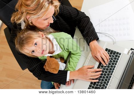 Family Business - telecommuter Businesswoman and mother is working in the internet while her daughter looks to the viewer
