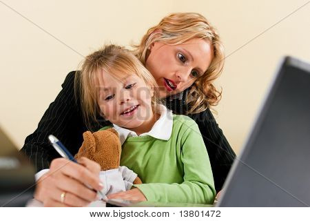 Family Business - telecommuter Businesswoman and mother is working in the internet while her daughter is playing with her teddy