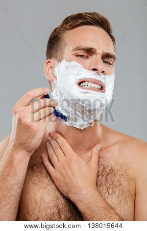Handsome young man scares to shave isolated on the gray background