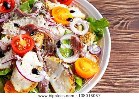 Ceasar salad with grilled chicken fillets, red onion rings, lettuce, orange cherry tomatoes, croutons, grated parmesan cheese, seasoned with anchovy fillets.