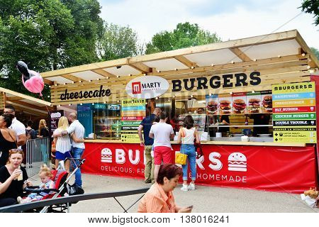 CLUJ-NAPOCA ROMANIA - JULY 9 2016: People have a snack at the Street Food Festival in central park Cluj. Vendors in stalls sell tasty fast food from different cultures.