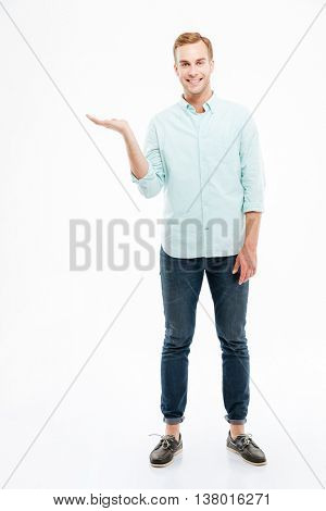 Full length portrait of happy handsome confident cheerful attractive young man holding copyspace on the palm over white background