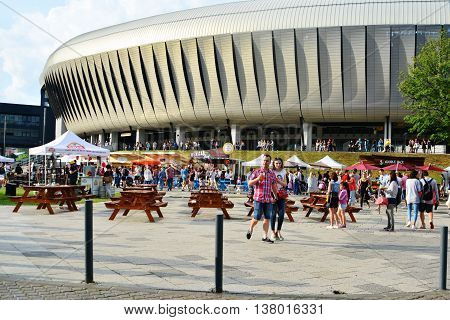 CLUJ-NAPOCA ROMANIA - JULY 9 2016: People have a snack at the Street Food Festival in front of the Cluj Arena stadium in central park Cluj. Vendors in stalls sell fast food from different cultures.