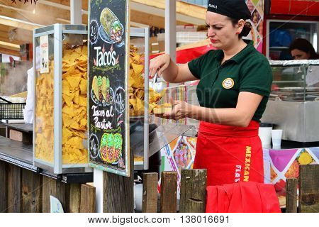 CLUJ-NAPOCA ROMANIA - JULY 9 2016: Vendor woman sells Mexican food at the Street Food Festival Cluj.