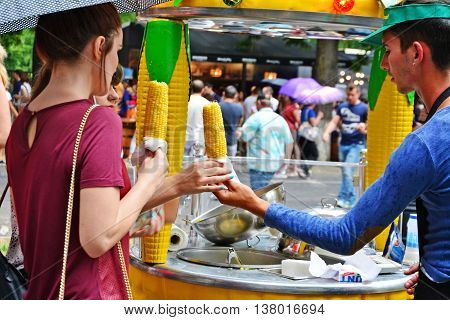 CLUJ-NAPOCA ROMANIA - JULY 9 2016: Vendor sells cooked corn on the cob to young women customers at the street food festival.