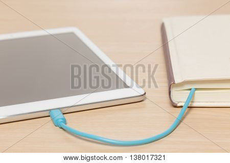 Tablet connected to the old book with a cable and download information from there