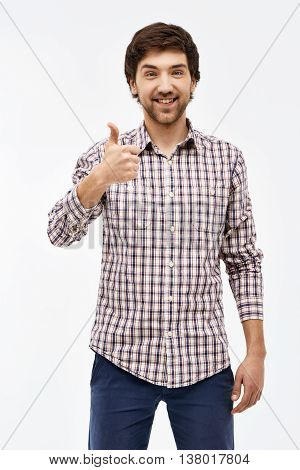 Close-up portrait of handsome happy young blue-eyed dark-haired man wearing casual plaid shirt and jeans looking at camera showing thumb up. Isolated on white background.