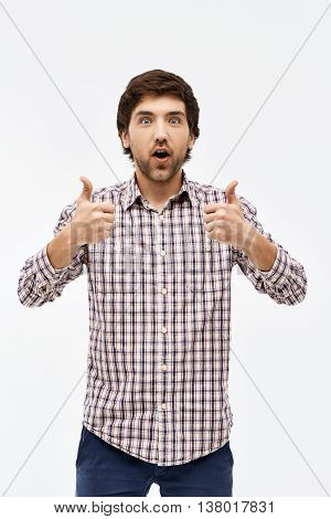 Close-up portrait of handsome surprised young blue-eyed dark-haired man wearing casual plaid shirt and jeans looking at camera showing thumbs up. Isolated on white background.