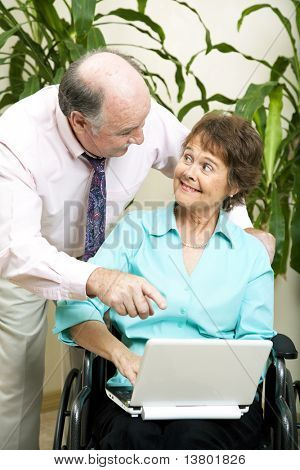 Secretary in wheelchair, typing on her laptop computer while her boss looks on.