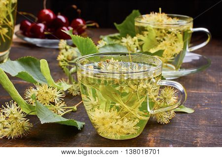 Two glass cups of linden tea with fresh flowers on dark wooden baskground. Top view.
