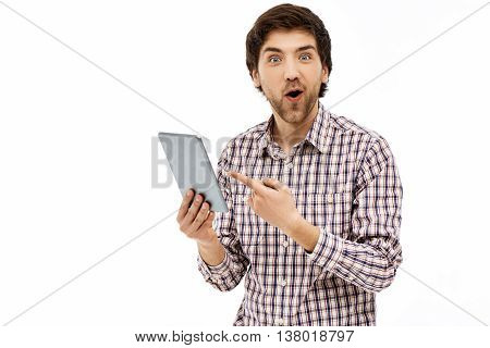 Close-up portrait of handsome surprised young blue-eyed dark-haired man wearing casual plaid shirt pointing on tablet which he holds in one hand. Looking at camera. Isolated on white background.