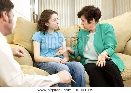 Teenage girl and her mother meeting in a family therapist's office for counseling.