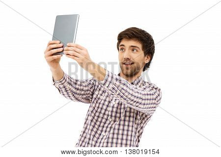 Close-up portrait of handsome smiling young blue-eyed dark-haired man wearing casual plaid shirt holding tablet in hands making selfie. Isolated on white background.
