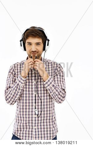 Close-up portrait of a handsome confident blue-eyed dark-haired young man wearing casual plaid shirt singing in head phones. Looking in camera. Isolated.