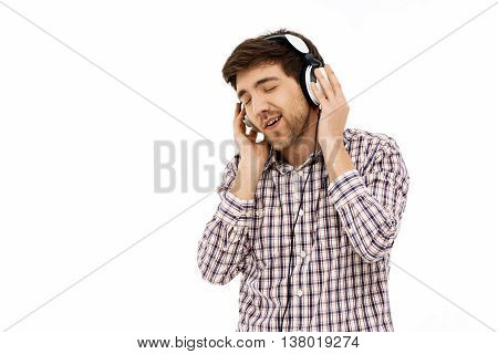 Close-up portrait of handsome romantic young man wearing casual plaid shirt singing in head phones. Isolated.